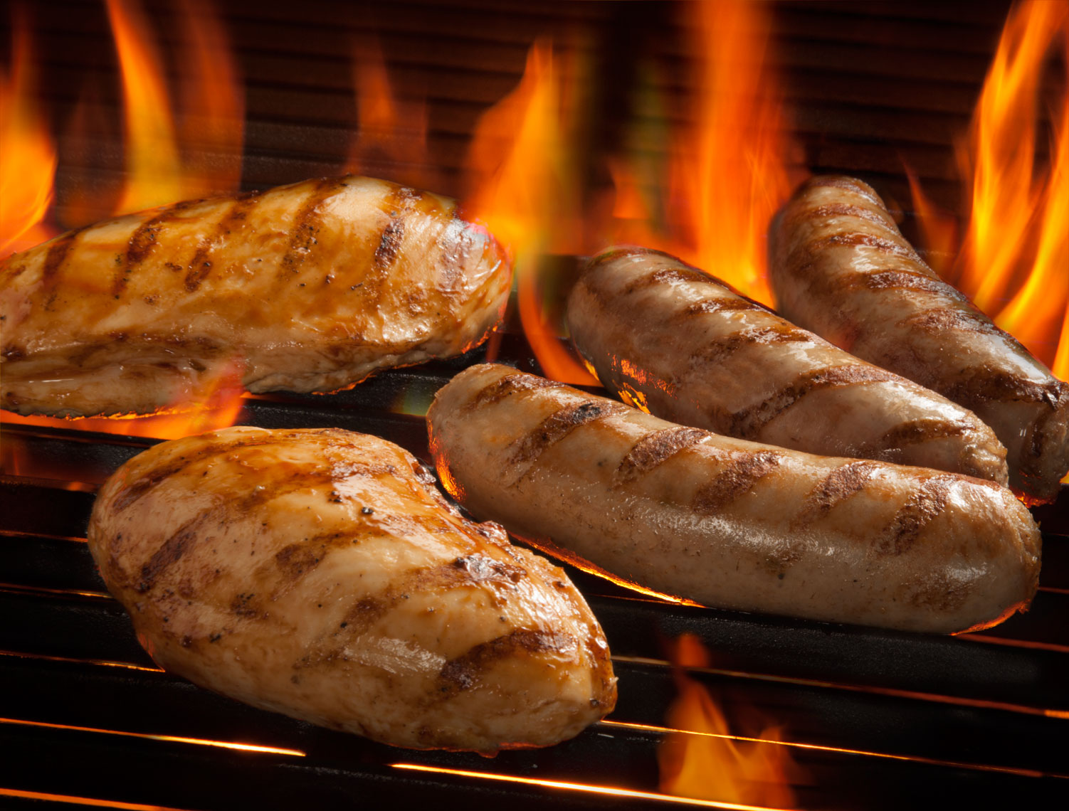 Chicken and sausages on flaming grill